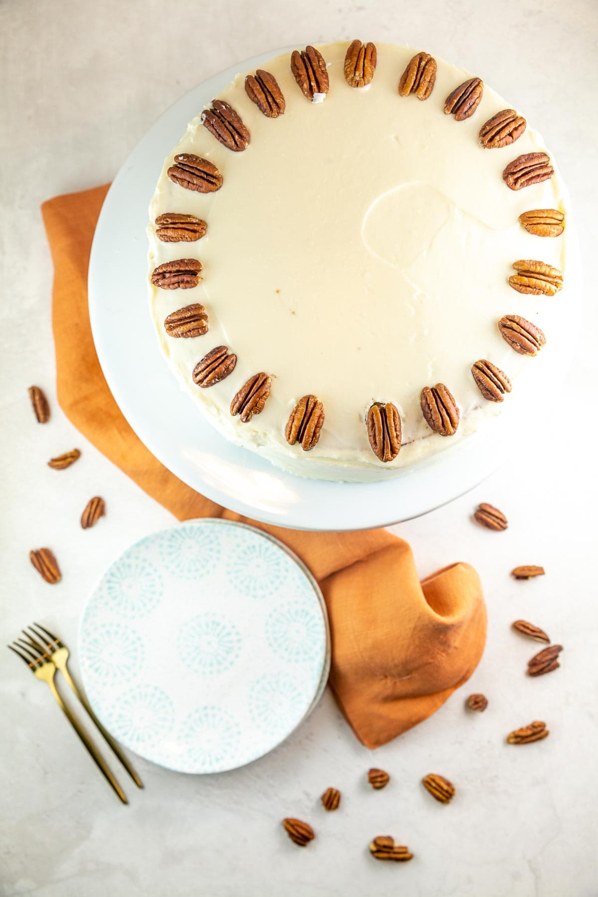 cake decorated with smooth cream cheese frosting and halved pecans