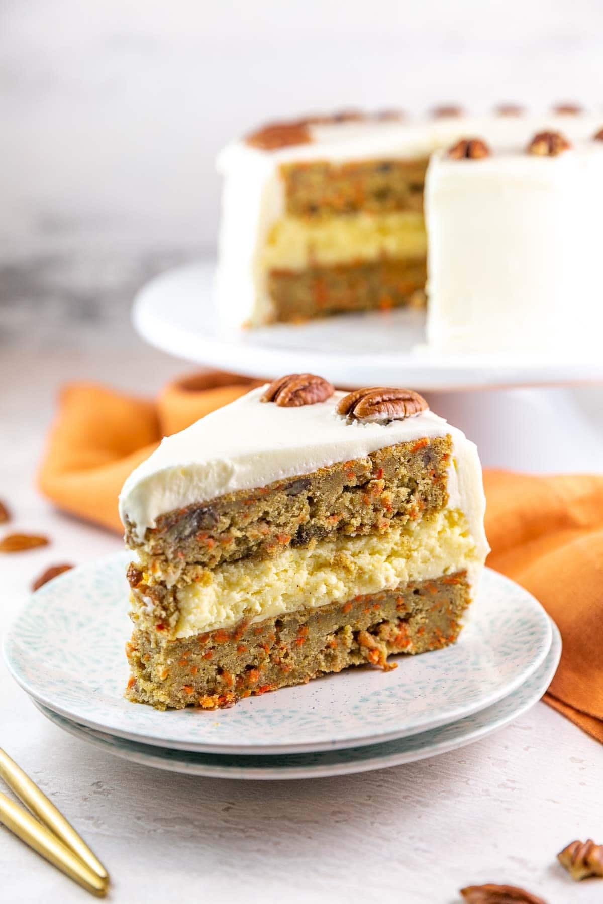 a slice of a cake with two layers of carrot cake and one layer of cheesecake