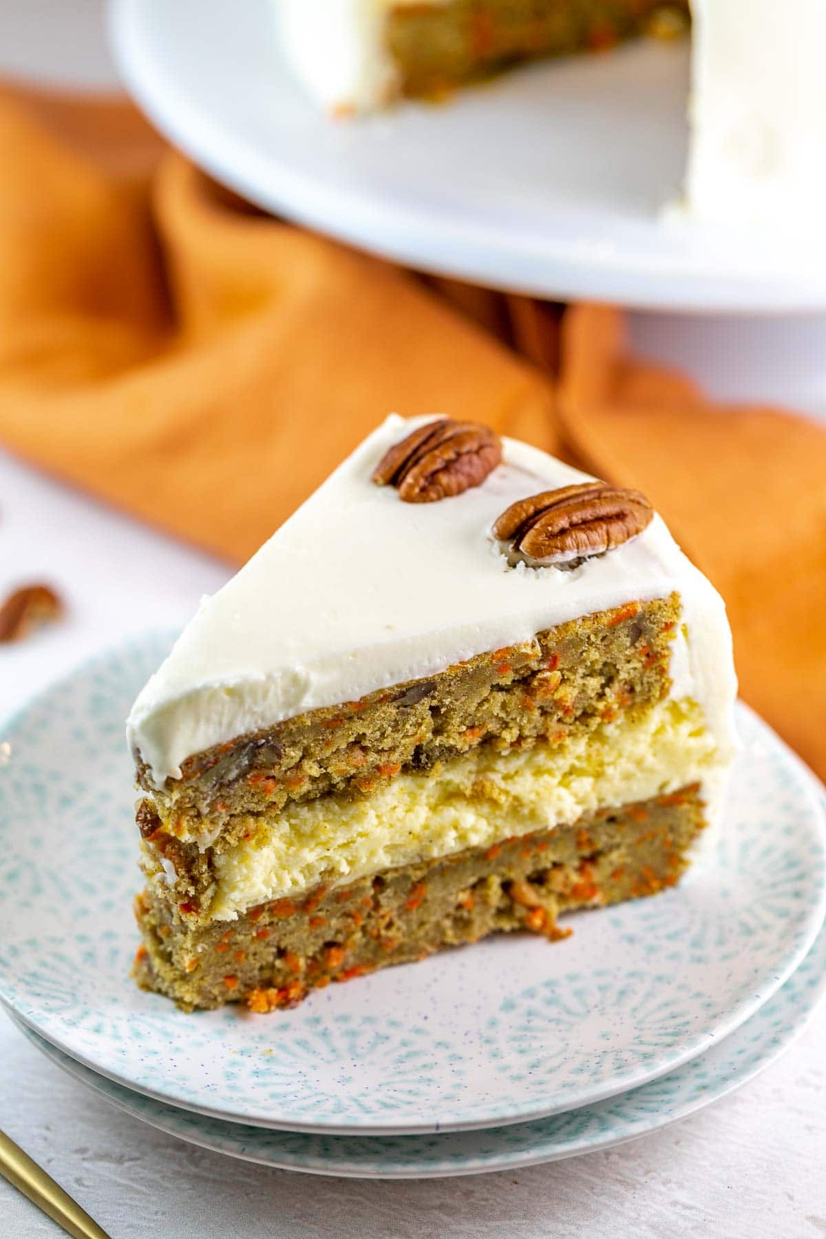 slice of cake with two slices of carrot cake and a layer of cheesecake in the middle