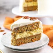 carrot cake cheesecake cake with two layers of carrot cake and a cheesecake in the middle