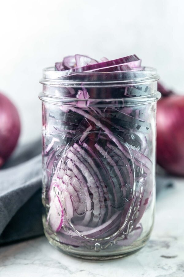 glass jar filled with thinly sliced red onion