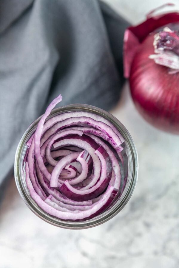 overhead view of sliced onions filling a glass jar