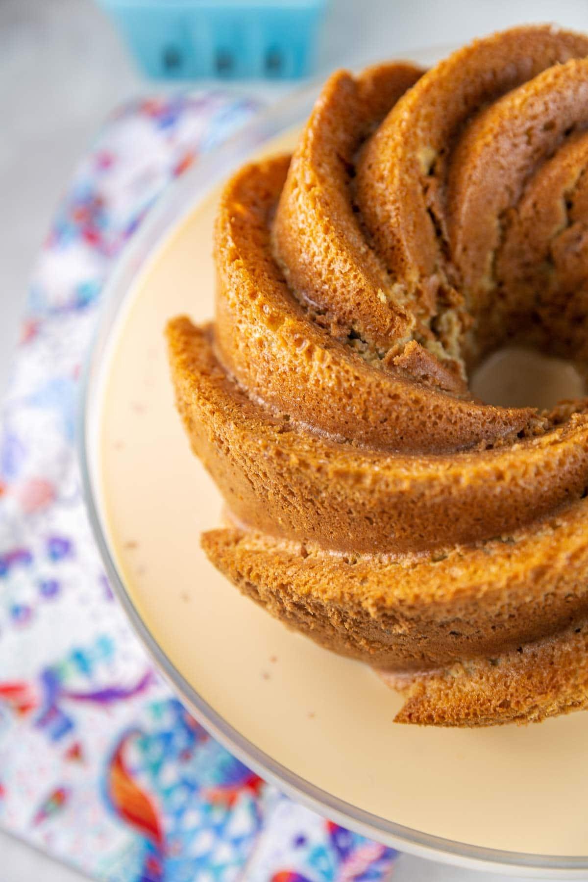 sponge bundt cake sitting on a plate soaking up tres leches milk mixture
