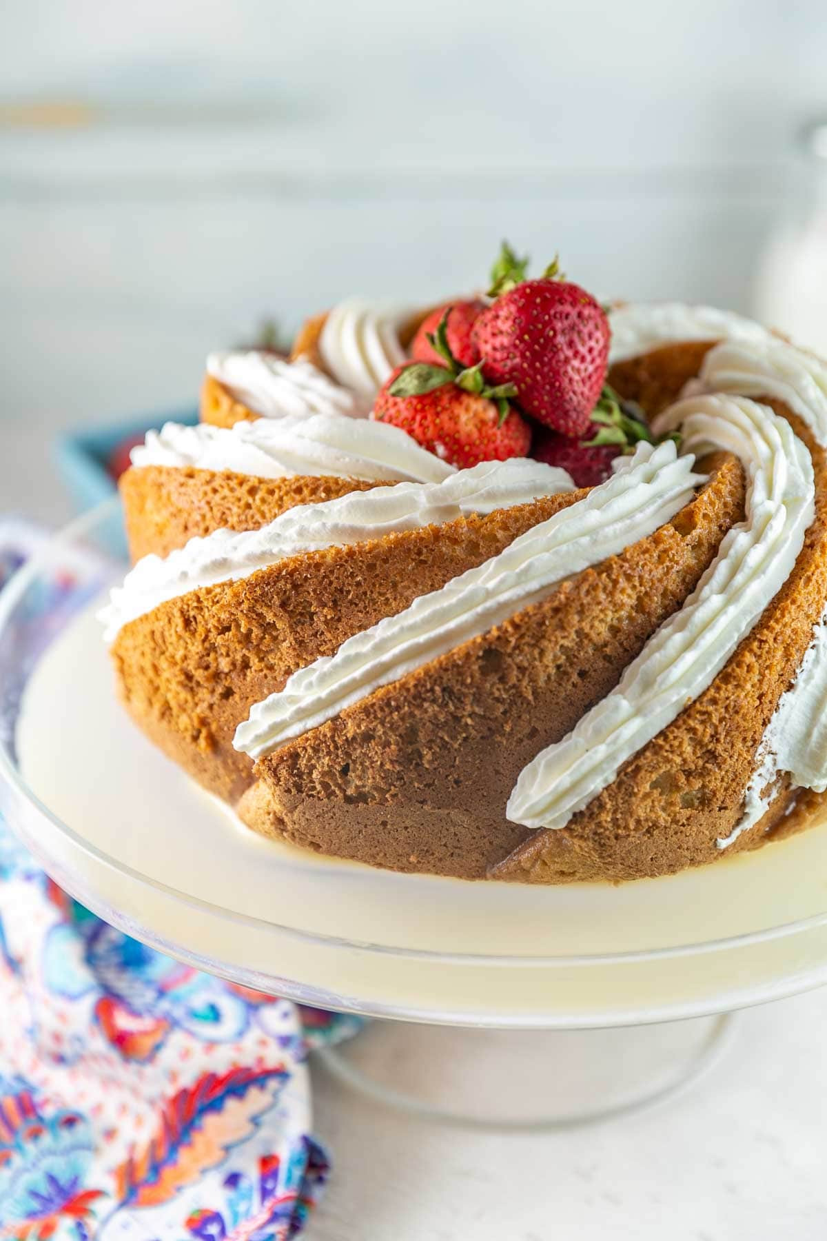 sponge cake baked in a bundt pan soaked in milk and decorated with whipped cream and strawberries