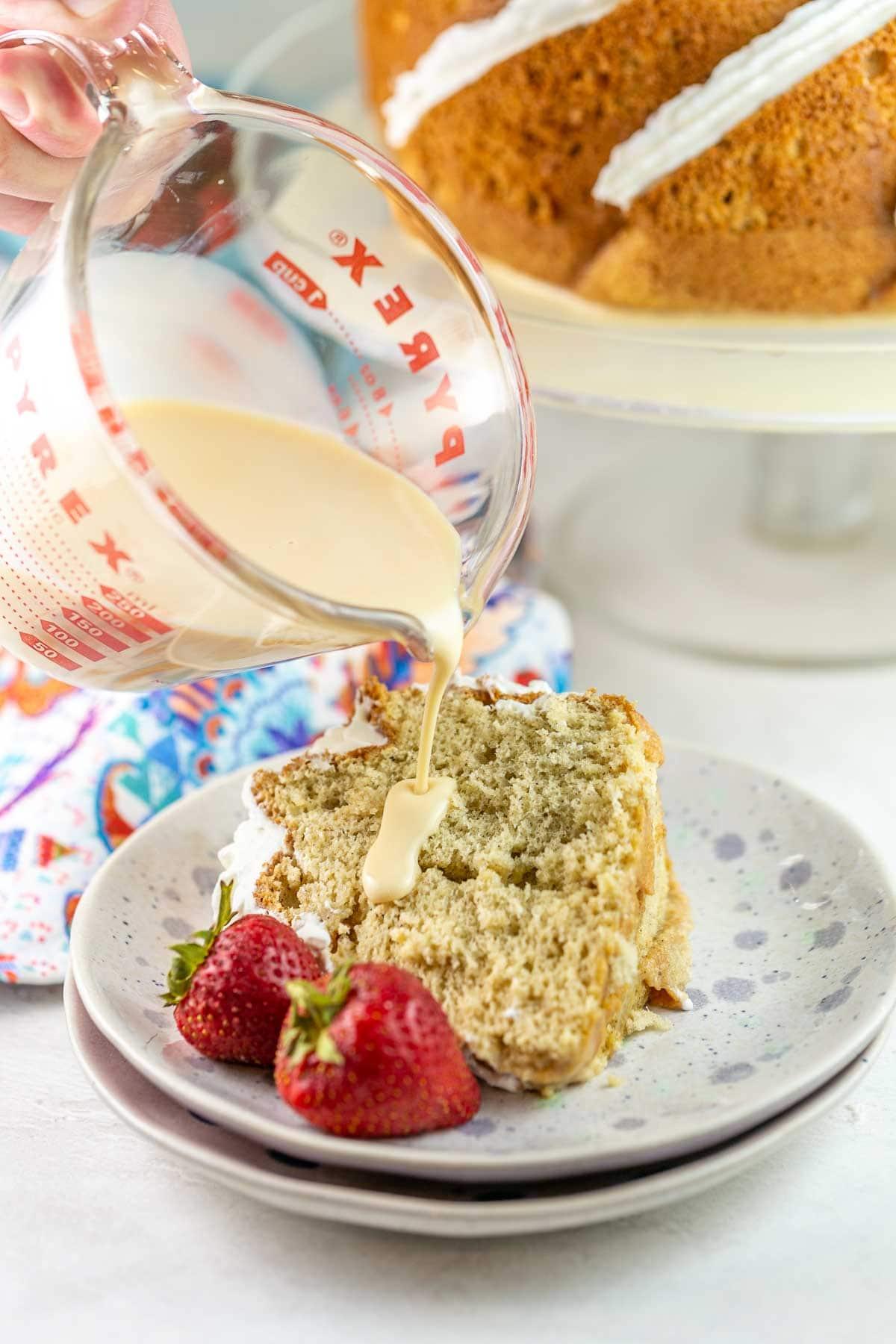 pouring extra milk mixture onto a slice of bundt cake