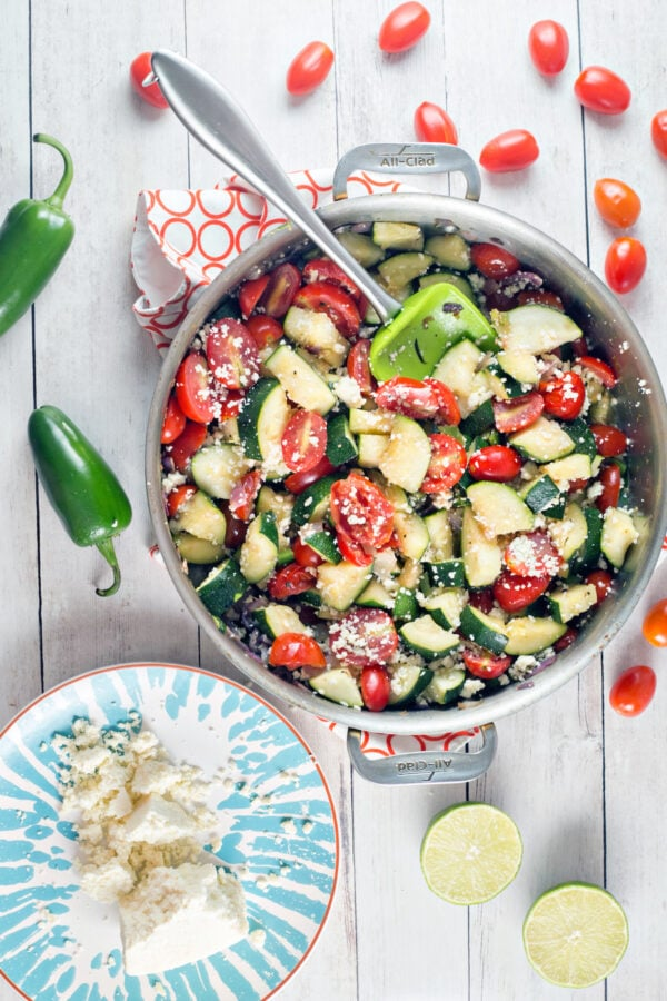 large skillet full of zucchini, tomatoes, and jalapenos
