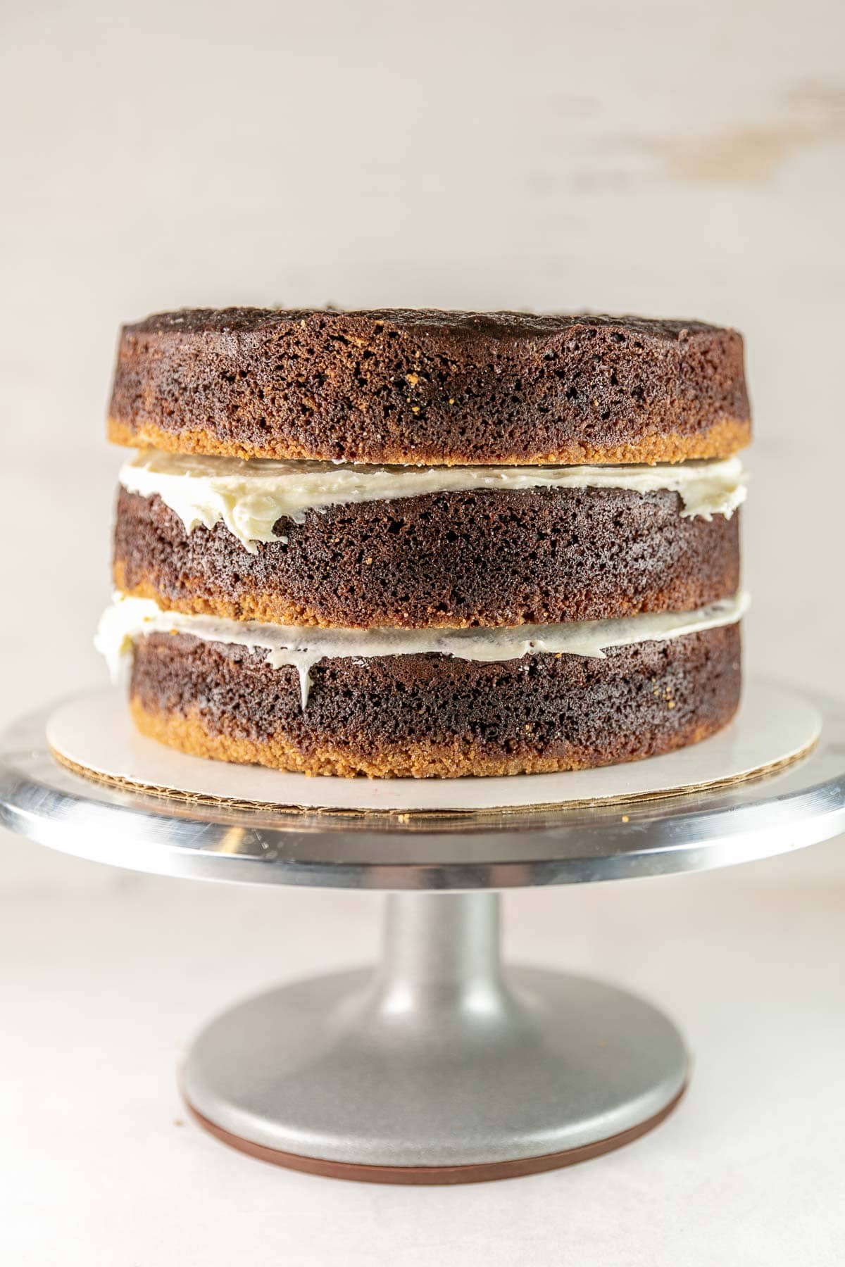 three layers of chocolate graham cracker cake stacked before frosting