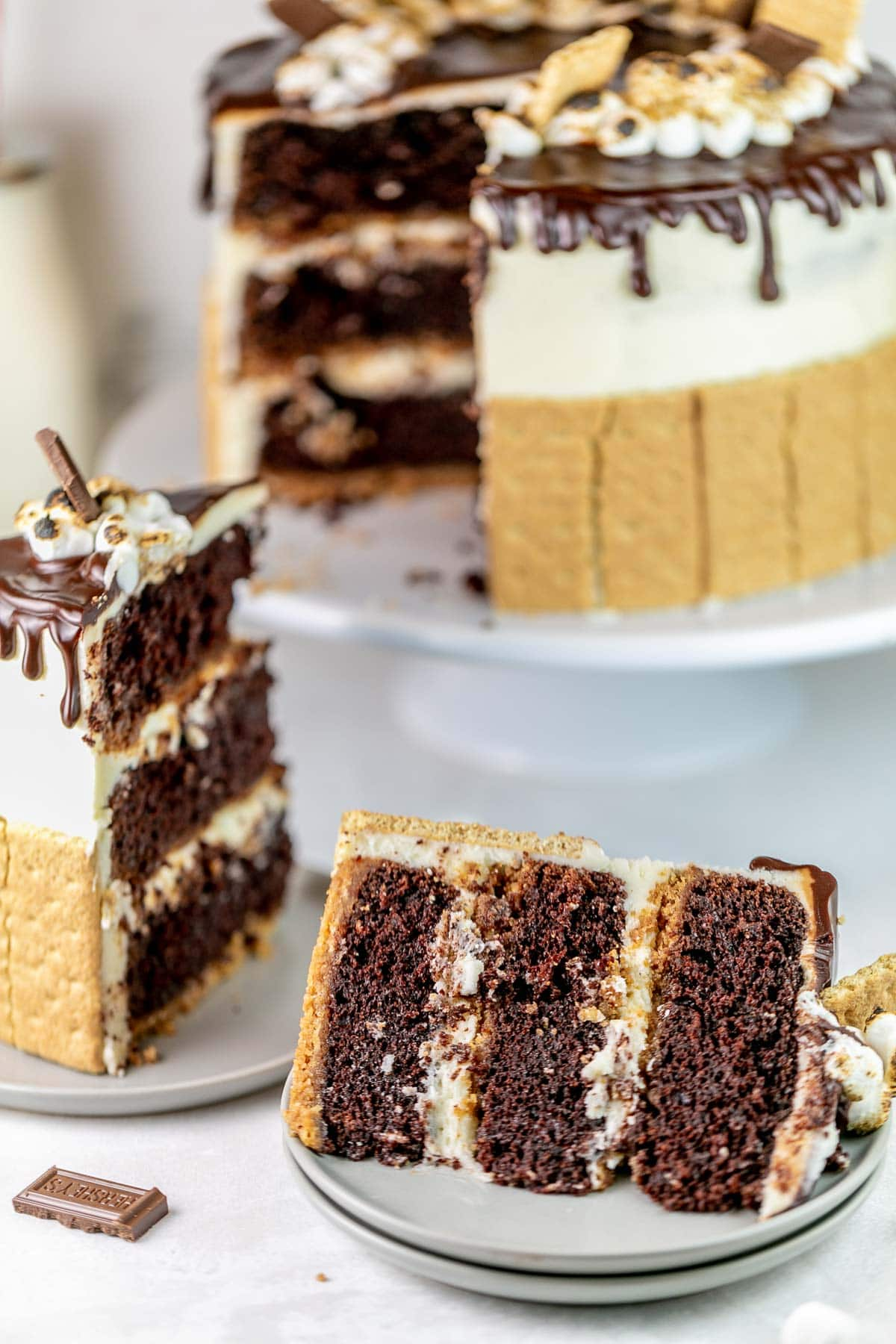 slice of three layer chocolate cake with a graham cracker crust and marshmallow buttercream