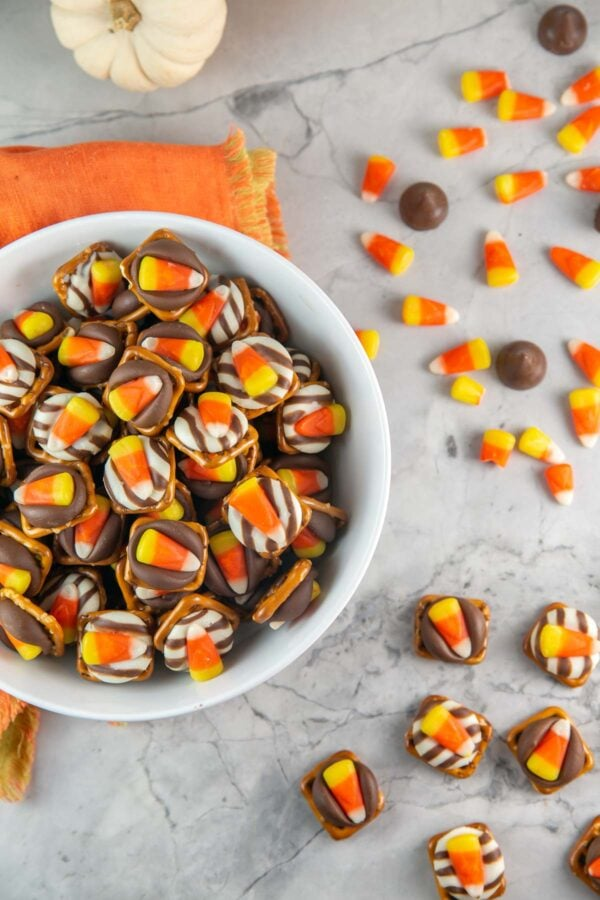 bowl of candy corn pretzel bites with candy corn and kisses scattered in the background