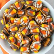 """Candy Corn Pretzel Bites: A pretzel, a kiss, and a piece of candy corn make the perfect easy Halloween treat! Make ahead and perfect for class parties, """"boo bags"""", or adult Halloween parties!"""