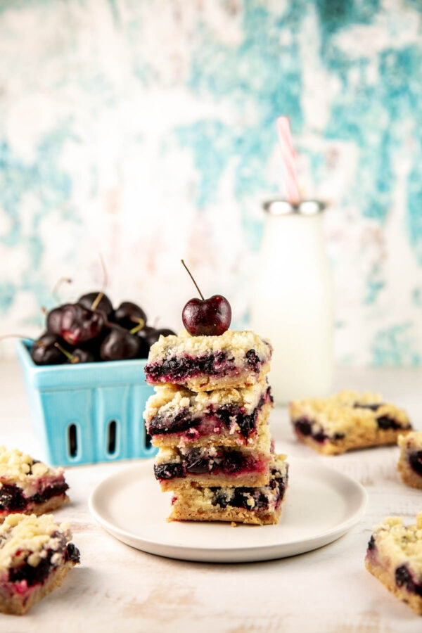 cherry pie bars on a plate with a basket of fresh cherries and a glass of milk