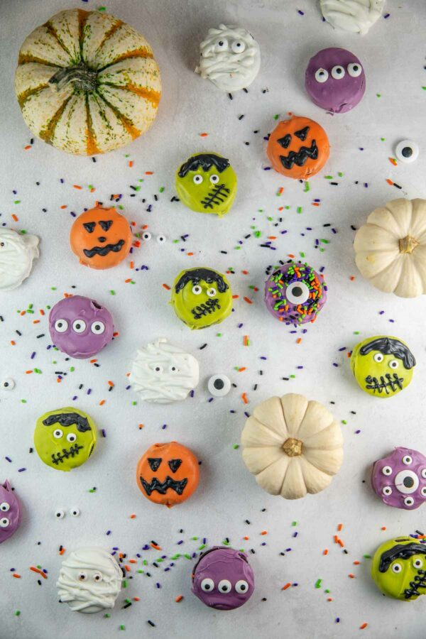 oreos dipped in chocolate and decorated for Halloween with sprinkles and pumpkins in the background