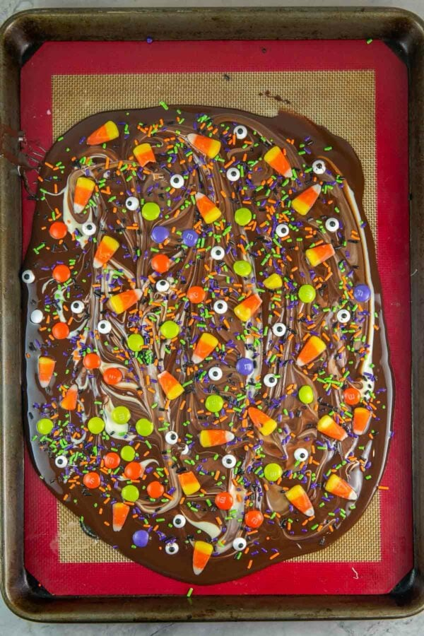 melted chocolate on a sheet pan covered with candy corn, sprinkles, eyeballs, and M&Ms
