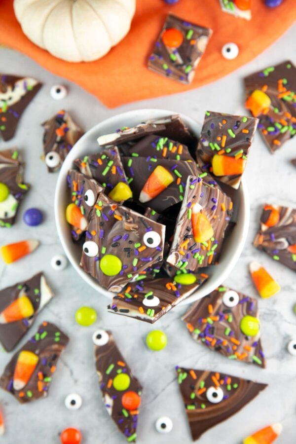 chocolate bark with candy corn, sprinkles, and candy eyes in a white bowl